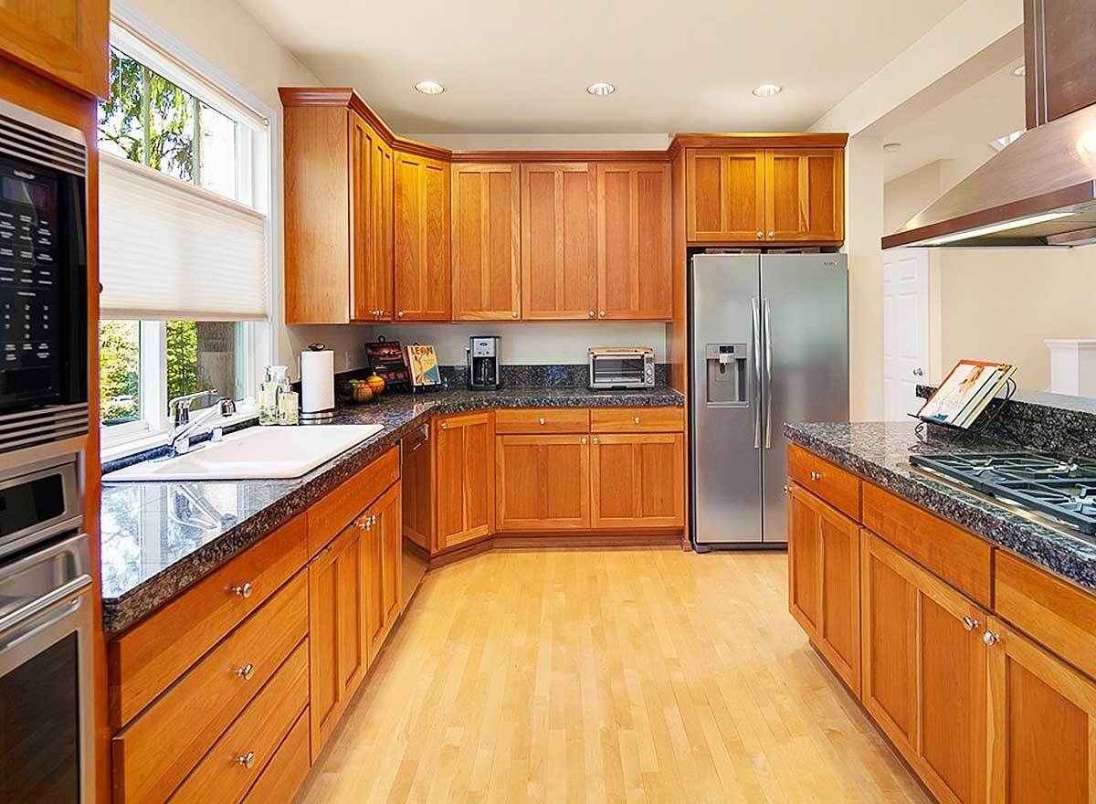 Kitchen with black granite countertops, wooden cabinets, a porcelain sink, and stainless steel appliances.
