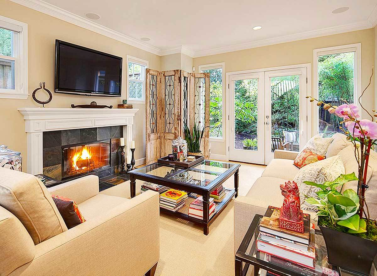 The living room has cozy beige seats, a glass top coffee table, and a wall-mounted TV fixed above the romantic fireplace.