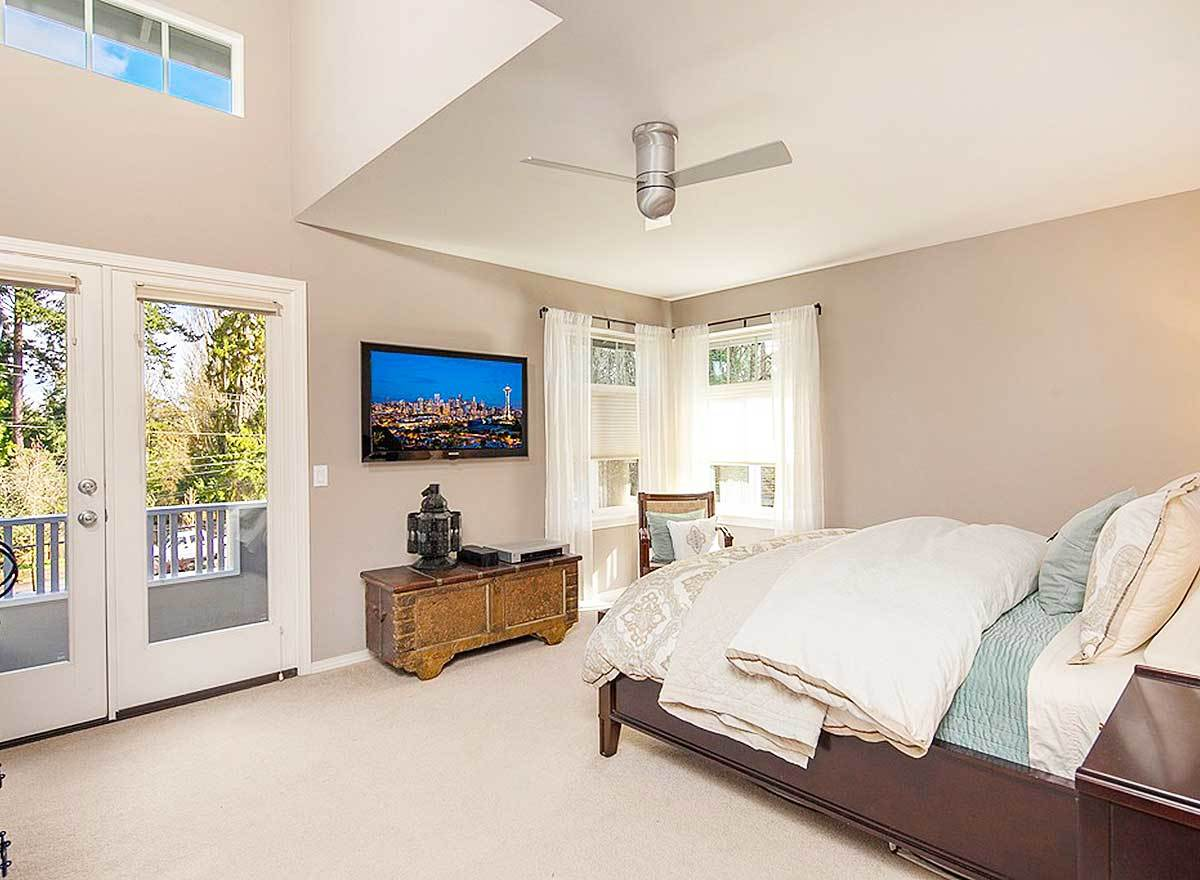 Primary bedroom with wooden furnishings, a flatscreen TV, and a private deck accessible via the french door.