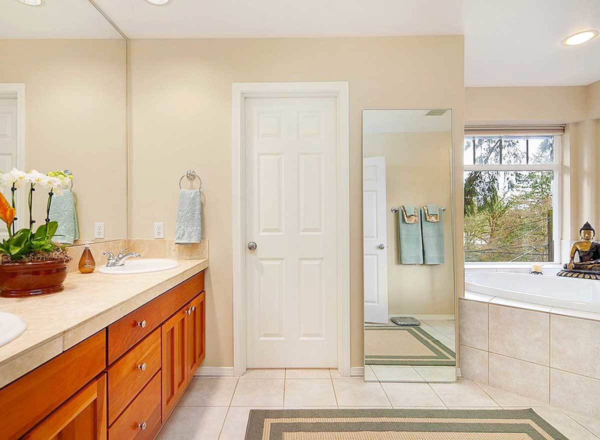 The primary bathroom is equipped with a dual sink vanity, a deep soaking tub, a full-length mirror, and a bordered area rug.
