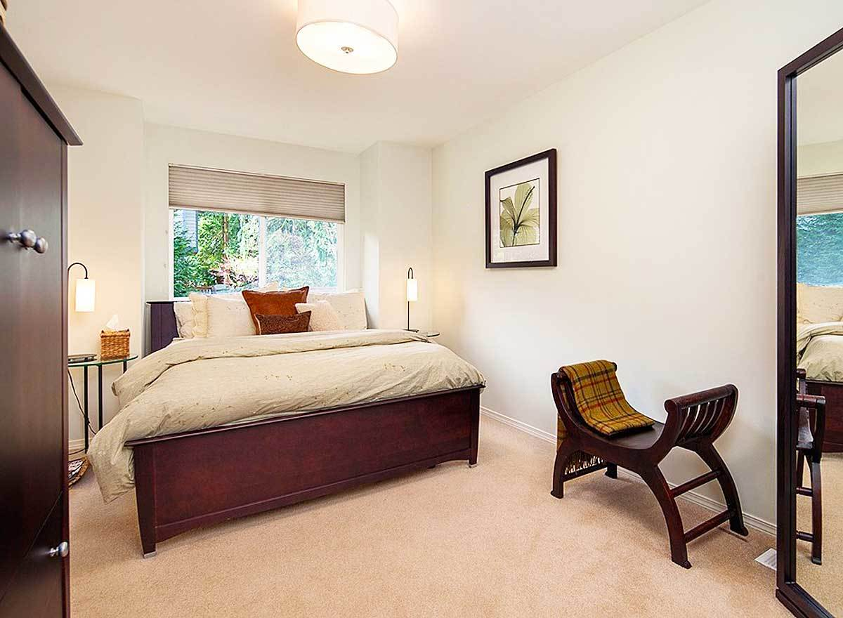 Another bedroom with wooden furnishings, beige carpet flooring, and pristine walls adorned with floral artwork.