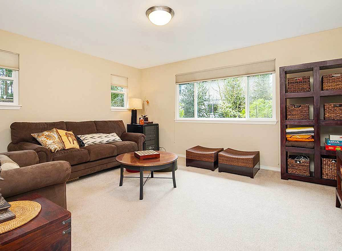 The recreation room is furnished with brown sectional and armchair, a round coffee table, cushioned stools, and a wooden shelving unit filled with storage baskets.