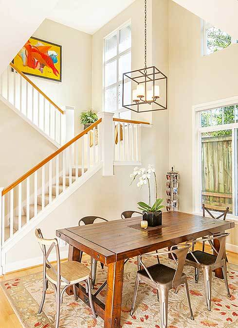 Dining room with a caged chandelier, a wooden dining table, and gray round back chairs sitting on a floral area rug.