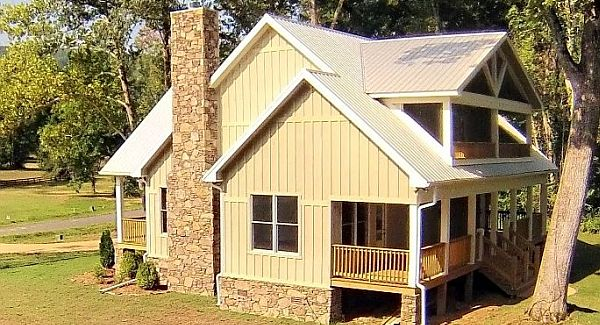 The angled side view shows the vertical siding and a stone chimney that matches the home's base.