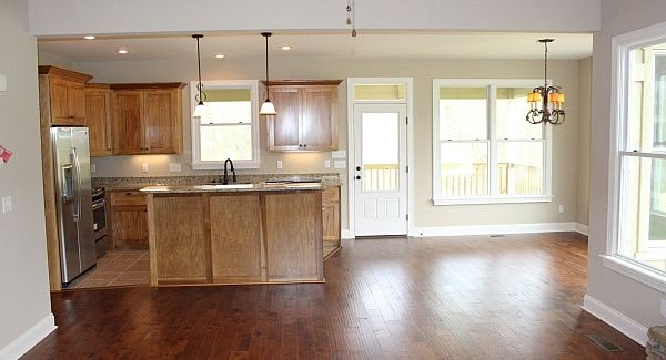 An open kitchen with a spare space on the side that's intended for the dining area.