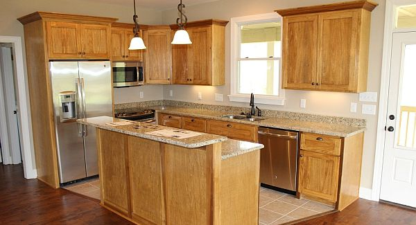 The kitchen offers wooden cabinets, stainless steel appliances, and a two-tier island bar.