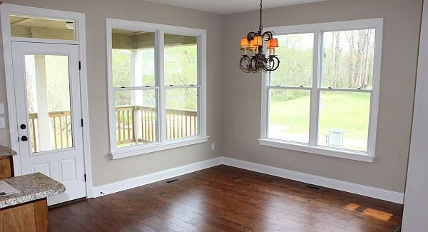 The dining space is flooded with natural light from the white-framed windows and the glass door that leads out to the back porch.