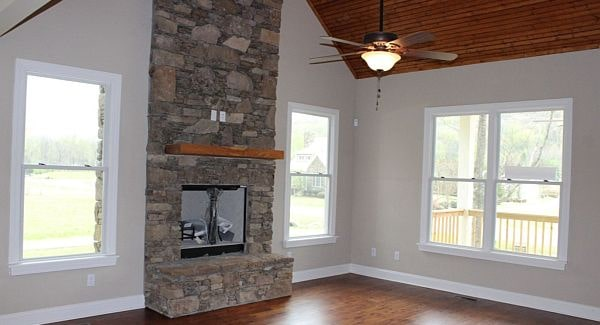Family room with a stone fireplace and a cathedral wood-paneled ceiling mounted with a fan.