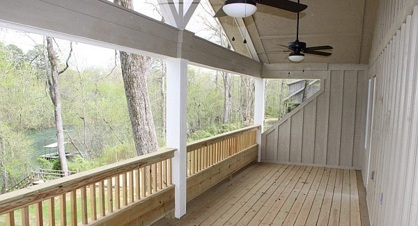 The covered porch is framed with decorative wooden trims and light wood railings that match the natural hardwood flooring.