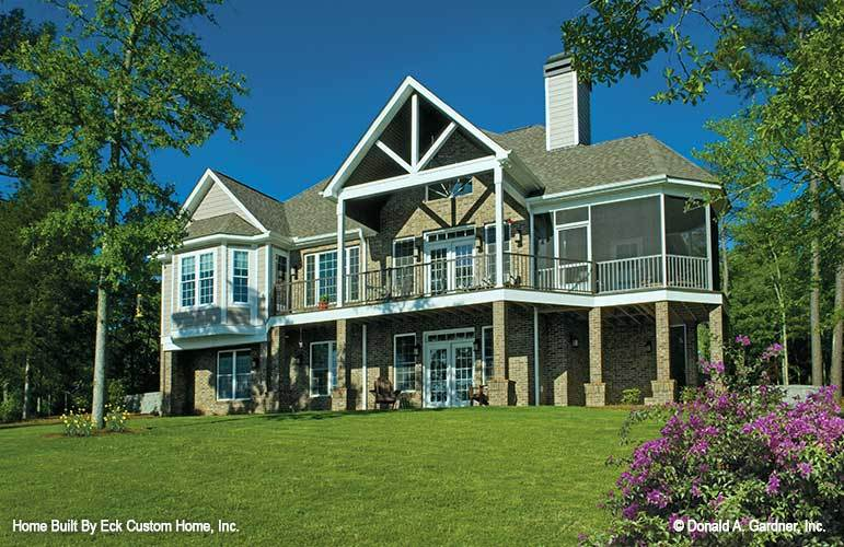 Rear exterior view showing the screened porch, wide deck, and expansive porch framed with stone columns.
