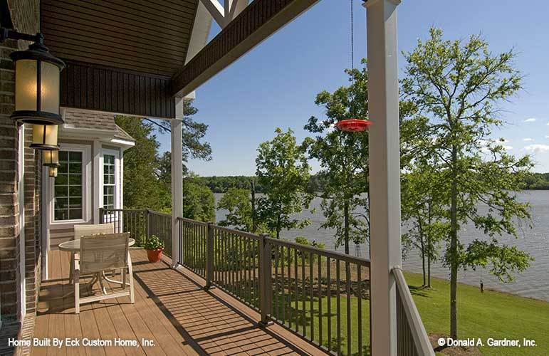 Back deck with round table and chairs, warm sconces, and a breathtaking lake view.