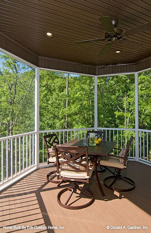 The screened porch is furnished with a wooden table and matching chairs topped with comfy cushions.