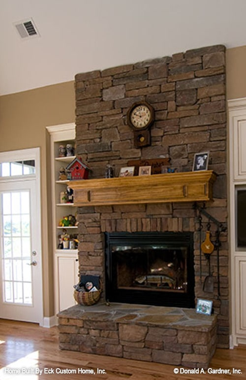 A closer look at the stone fireplace flanked by white cabinets.