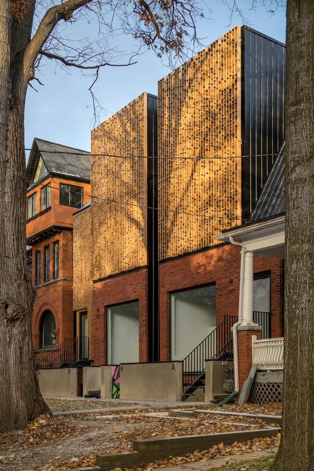 This is a look at the exteriors of the modern house showcasing the concrete low wall at the front contrasted by the brick facade of the base of the house.