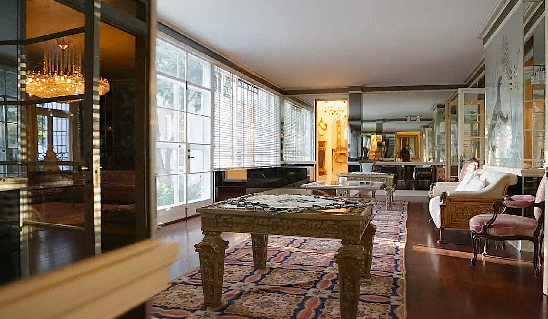 A seating area facing the gilded tables on area rugs and large windows. Image courtesy of Toptenrealestatedeals.com.