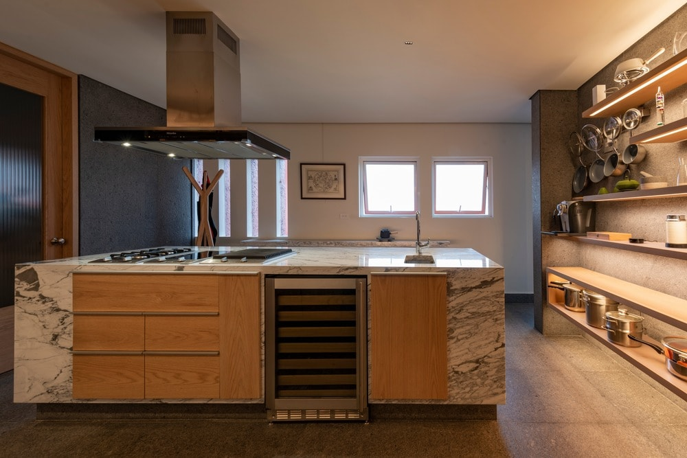 The kitchen has a large kitchen island with wooden cabinetry and a wine fridge.
