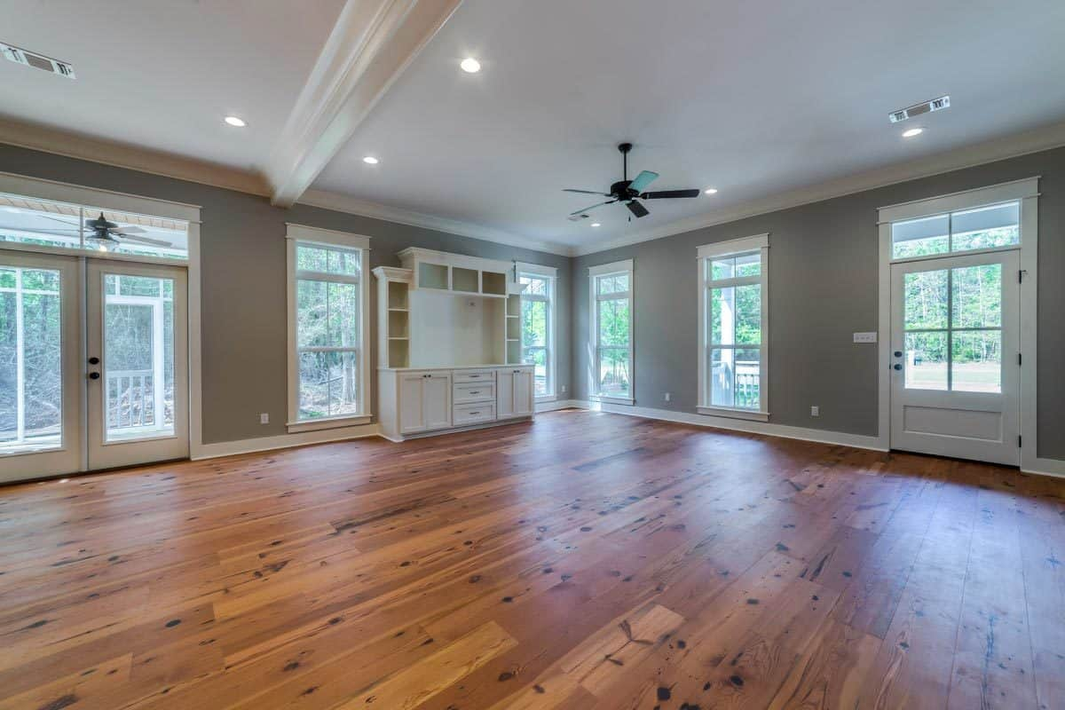 The great room has natural hardwood flooring and gray walls fitted with plenty of windows and glass doors to allow an ample amount of natural light in.