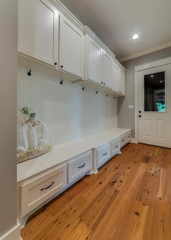 Mudroom with white cabinets, wrought iron coat hooks, and built-in storage bench fixed against the white beadboard wall.