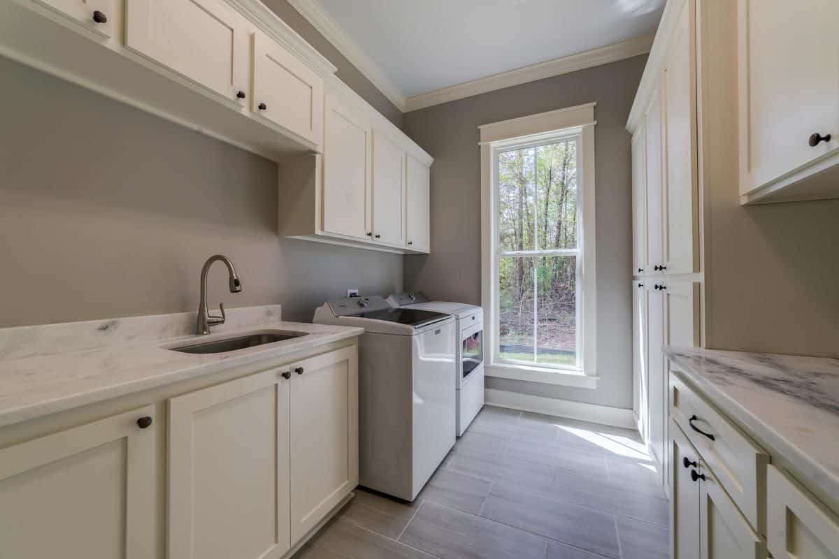 The utility room is equipped with white appliances, custom cabinetry, and an undermount sink fitted on the marble countertop.