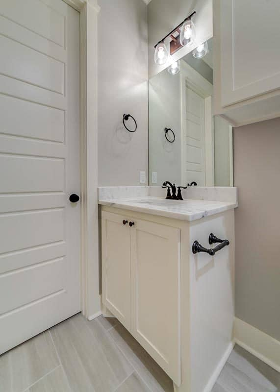 This bathroom offers a sink vanity with white marble countertop and wrought iron fixtures.