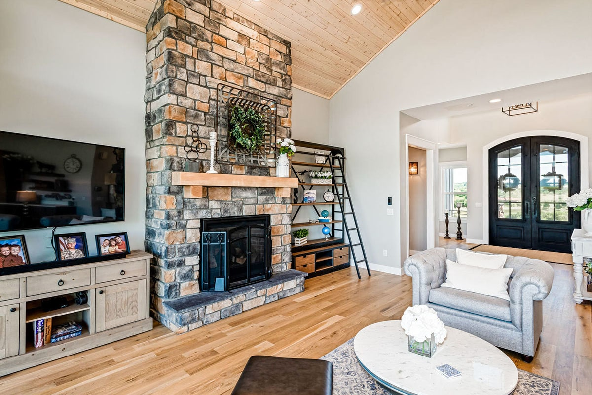 The living room offers cozy seats, a round coffee table, and a stone fireplace flanked by TV and a wooden shelving unit.