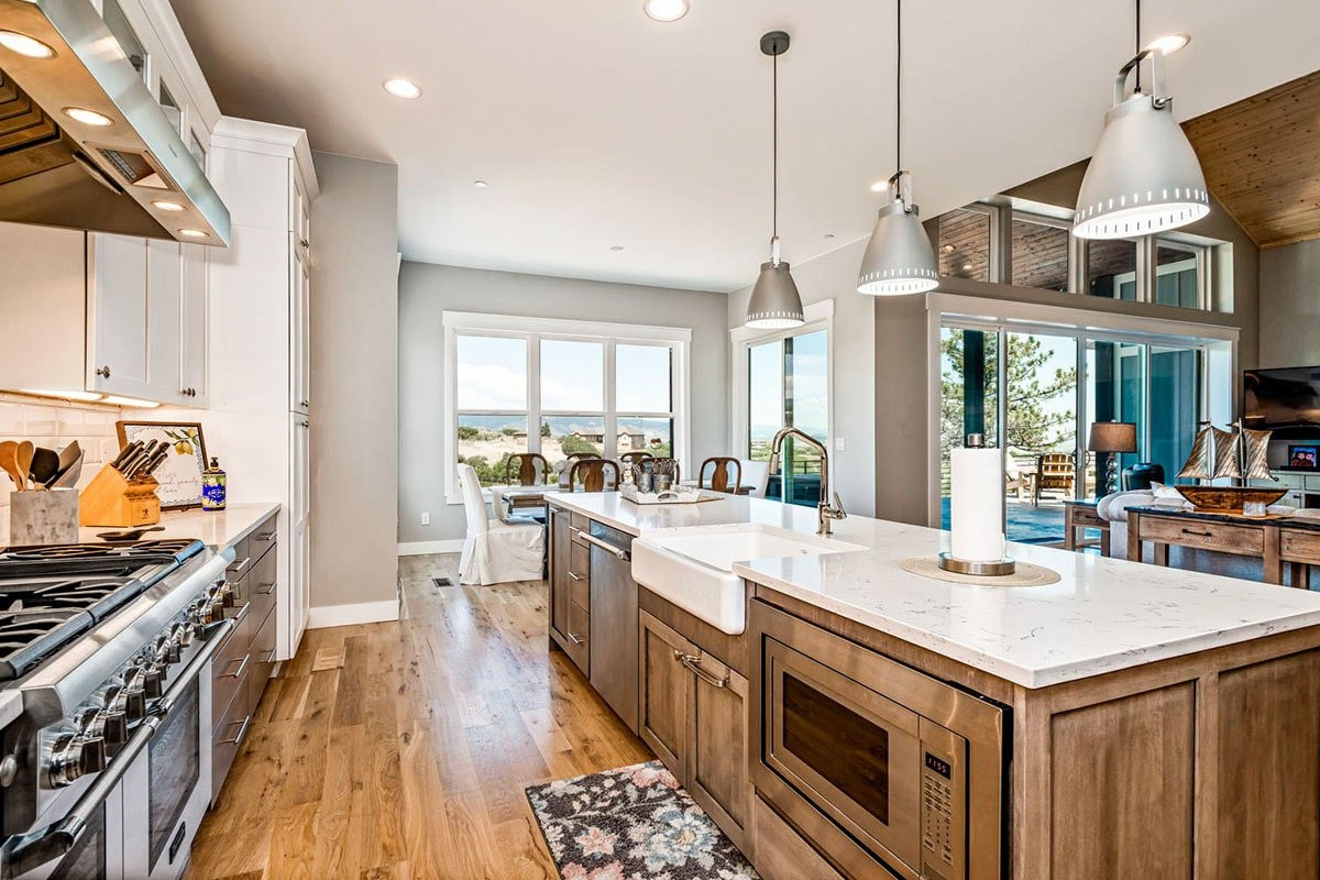 The center island is fitted with an oven, dishwasher, and a farmhouse sink.