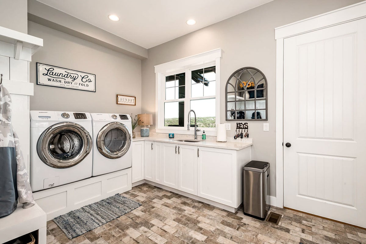 Utility room with white front-load appliances, marble countertops, undermount sink, and an arched mirror mounted against the gray wall.
