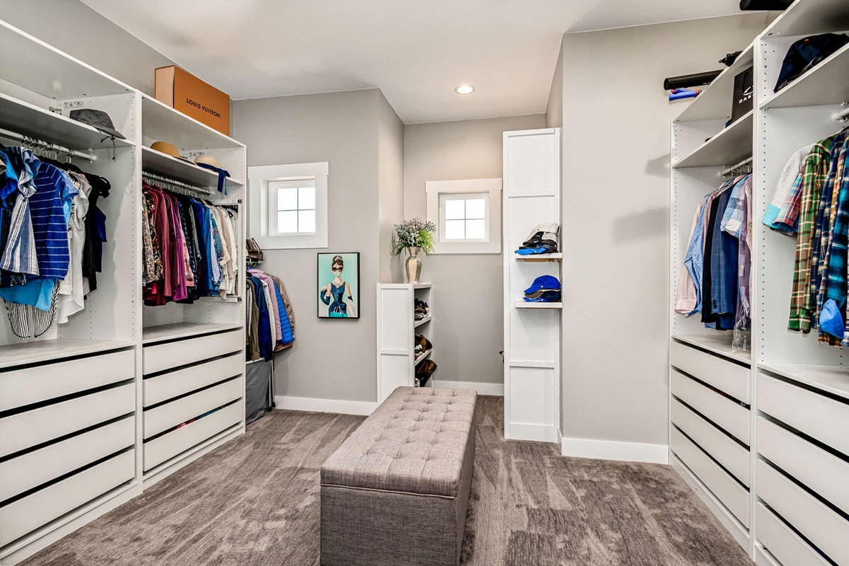 A large walk-in closet filled with custom shelvings and drawers surrounding a tufted ottoman.