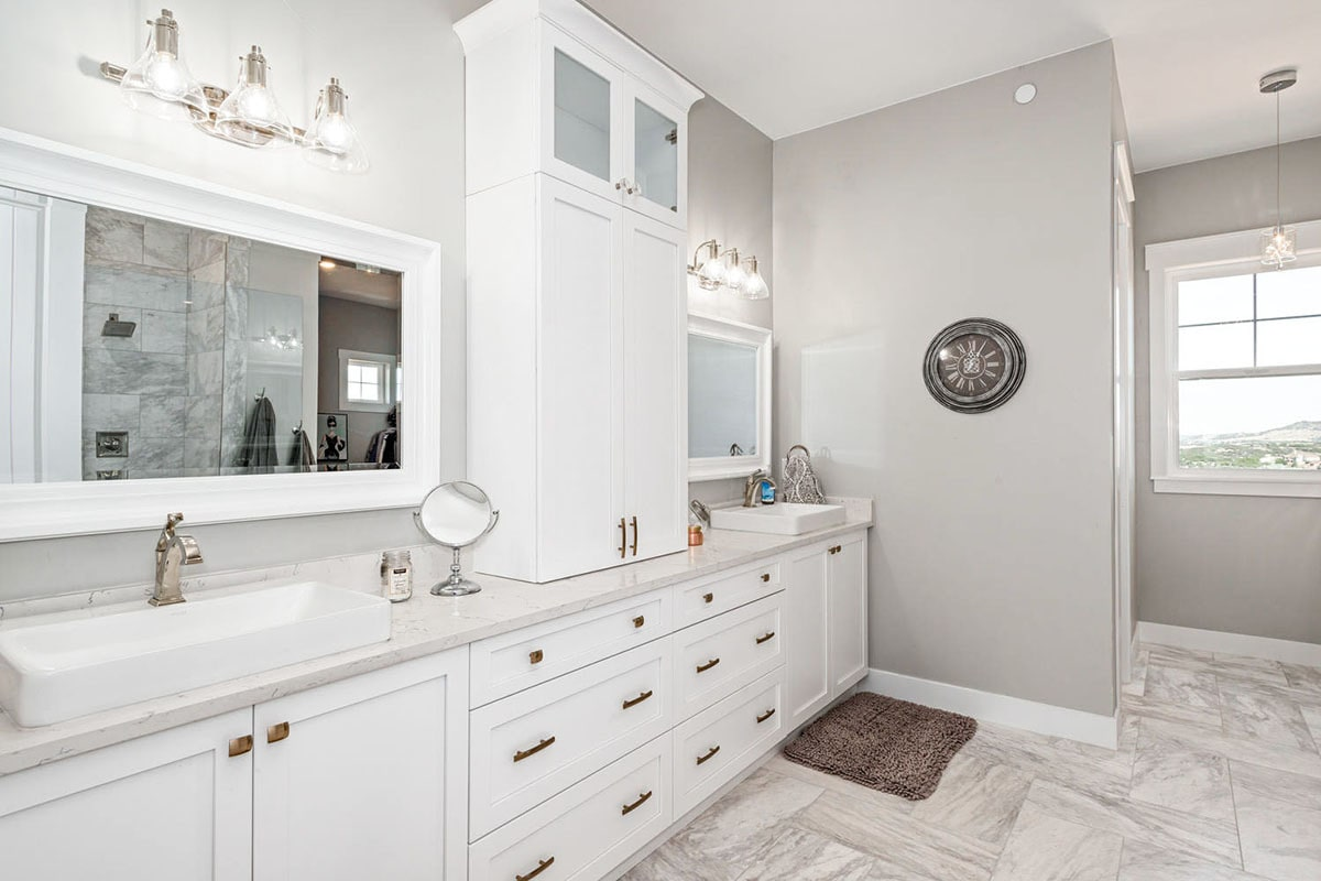 Primary bathroom with a walk-in shower and long sink vanity topped with two vessel sinks and a custom white cabinet.