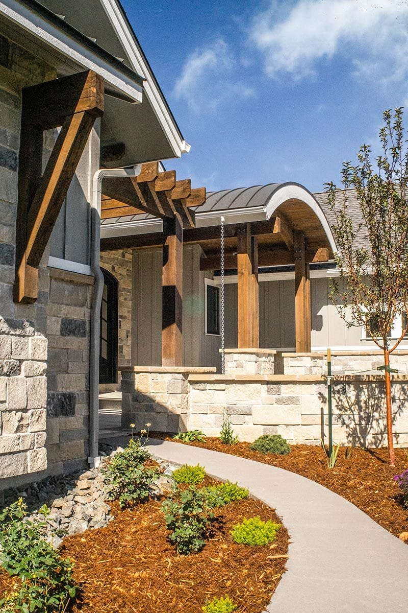 A concrete curved walkway leads to the home's front porch that's topped with a barrel roof.