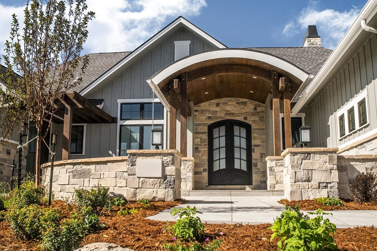 Home facade showing a board and batten exterior siding, stone accents, and an arched entry door fitted with glass panels.