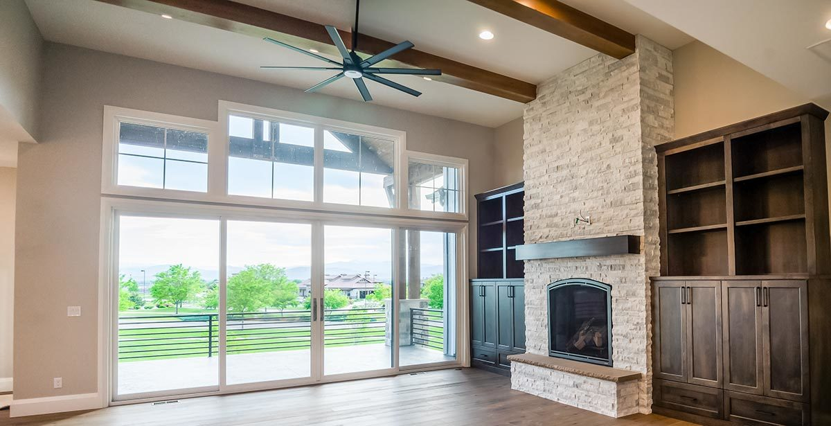 The living room has a stone fireplace, built-in cabinets, and a french door that opens out to the covered deck.