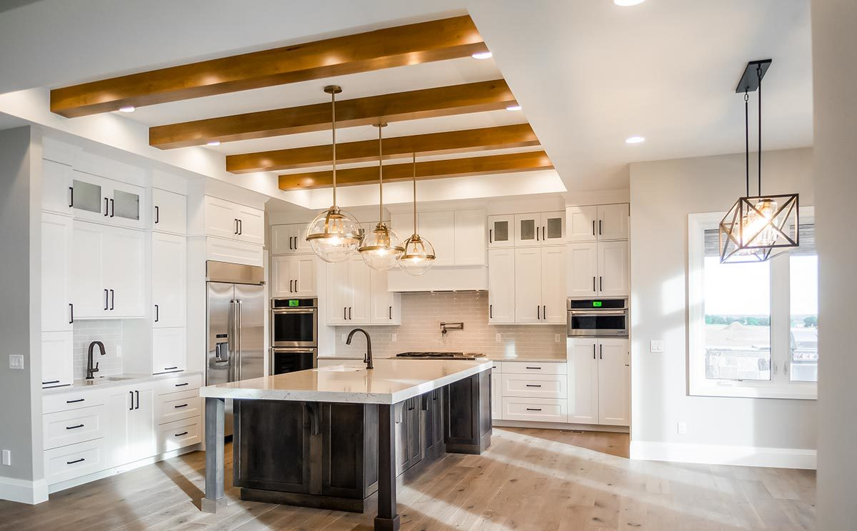 The kitchen is equipped with white cabinetry, stainless steel appliances, and a large center island topped with a sink.