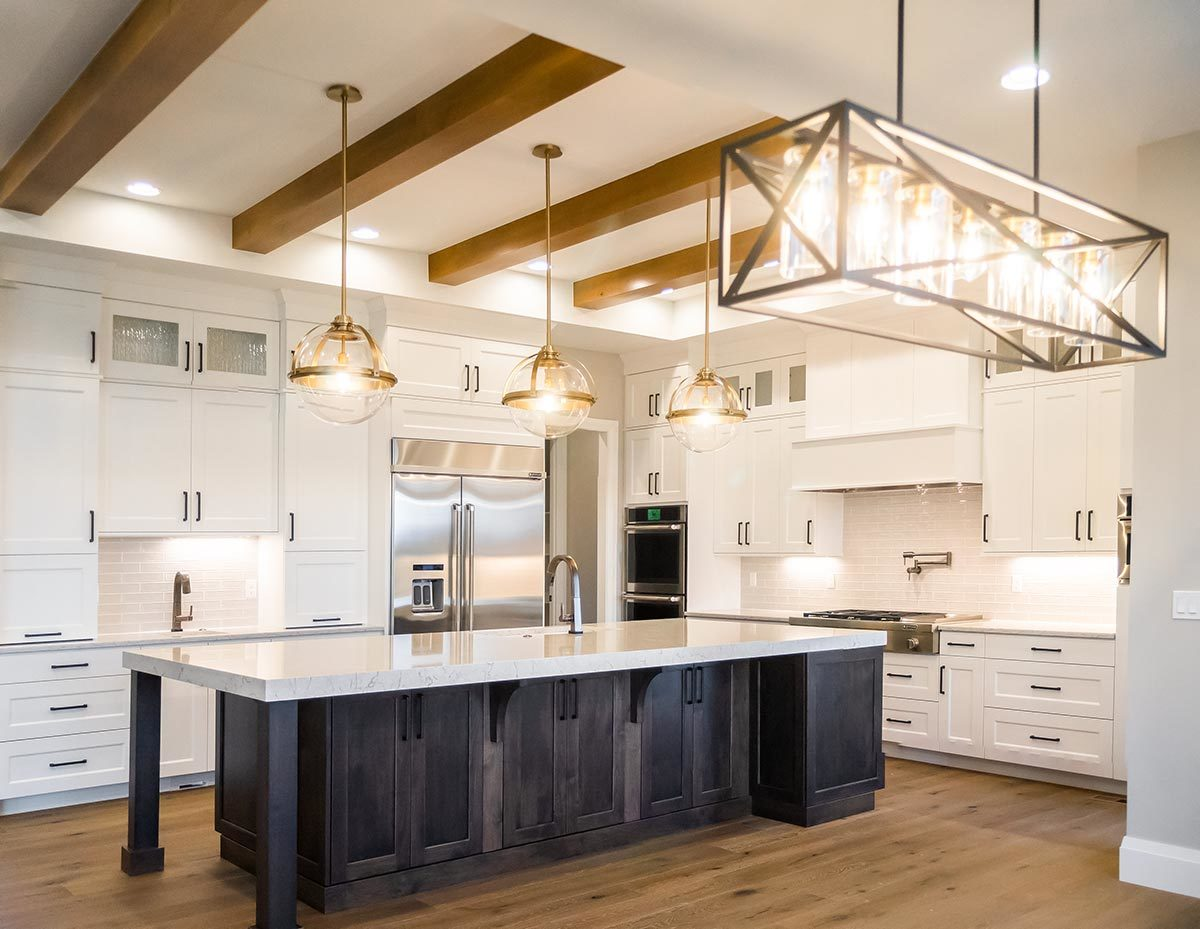 A linear chandelier along with glass globe pendants hanging from the beamed ceiling illuminate the kitchen.