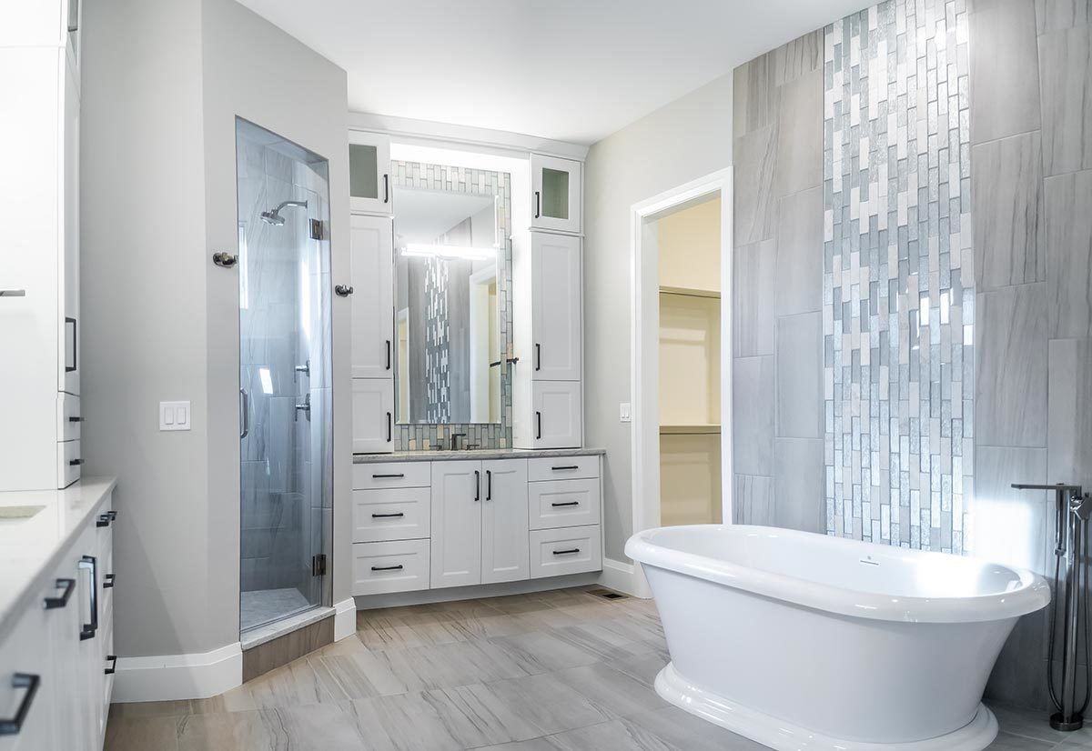 The primary bathroom offers a walk-in shower, two sink vanities, and a freestanding tub accentuated with striking linear mosaic tiles.