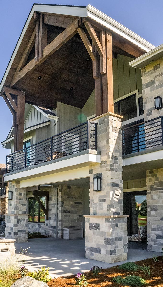 A closer look at the back porch and upper balcony enclosed in a gable roof and large tapered columns.