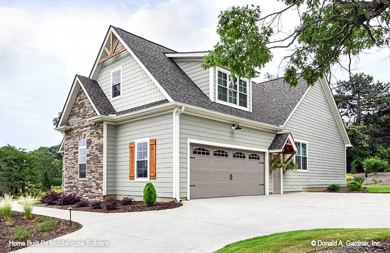 Home facade clad in gray exterior siding and striking stone accents. Decorative wood trims adorn the gable roof.
