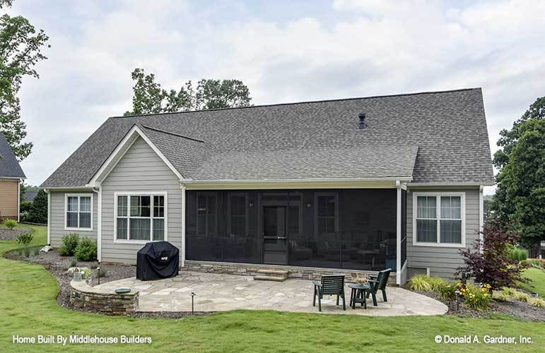 The rear view boasts a large screened porch and an open patio filled with built-in concrete bench and wooden chairs.