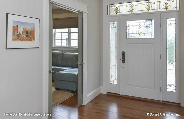 The foyer has a white front door graced with stained glass panels.