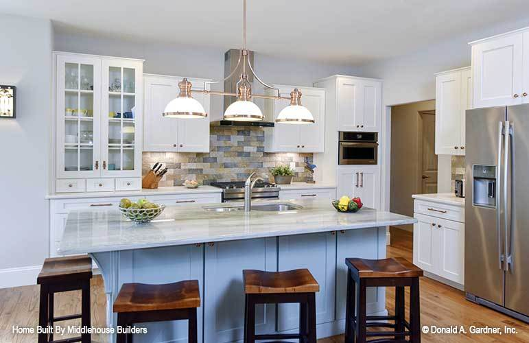 The kitchen is equipped with stainless steel appliances, white cabinetry, and a double bowl sink fitted on the breakfast island.