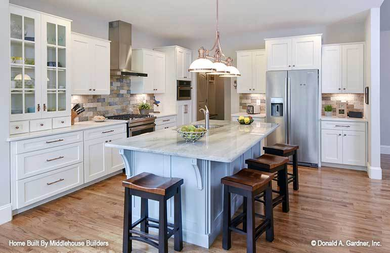 Chrome glass dome pendants hanging from the regular ceiling illuminate the kitchen.
