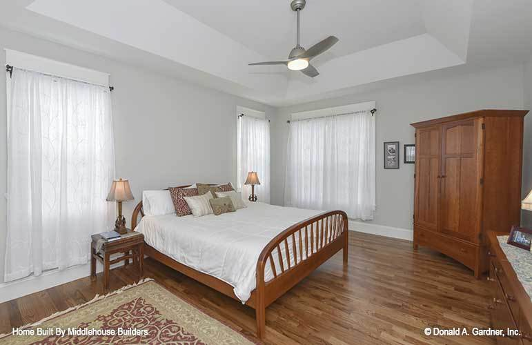 Primary bedroom with a tray ceiling and hardwood flooring that's topped with a tasseled area rug.