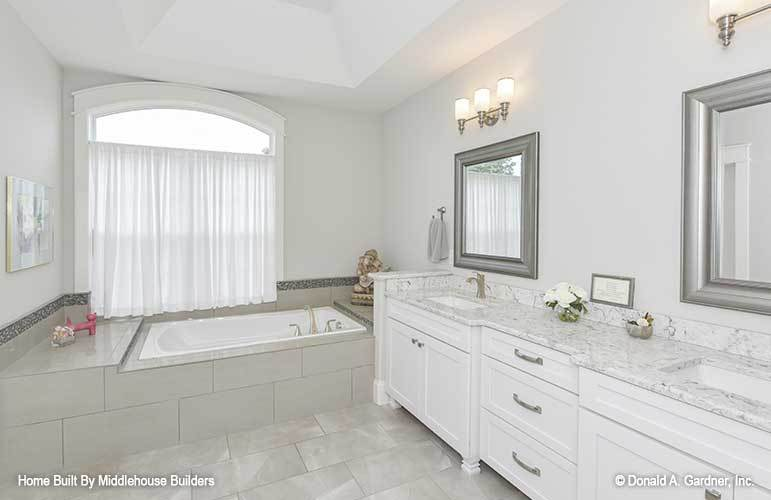 The primary bathroom has a deep soaking tub and a dual sink vanity paired with silver framed mirrors.