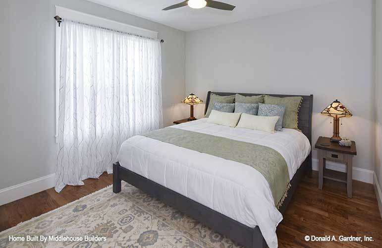 This bedroom offers a printed area rug and a gray wooden bed flanked with matching nightstands and stylish table lamps.