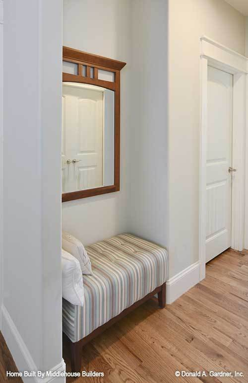 This nook has a hardwood flooring, a wooden framed mirror, and a striped tufted bench topped with white pillows.