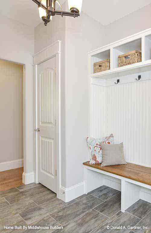 Mudroom with wide plank flooring and white beadboard wall fixed with built-in storage and seat.