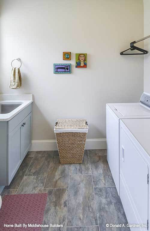 Utility room with white appliances, a rattan hamper, and an undermount sink fitted on the marble top counter.