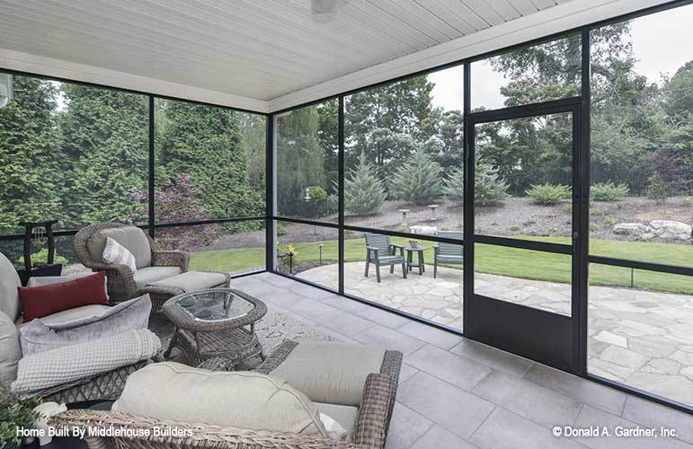The screened porch offers cozy wicker seats overlooking the open patio and its serene surrounding.