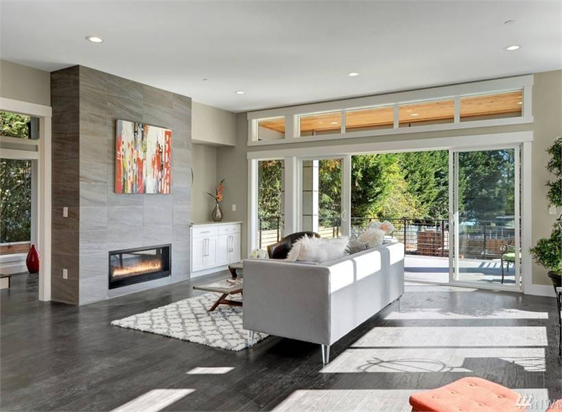The living room offers a sleek gray sofa, modern fireplace, and sliding glass doors that lead out to the spacious deck.