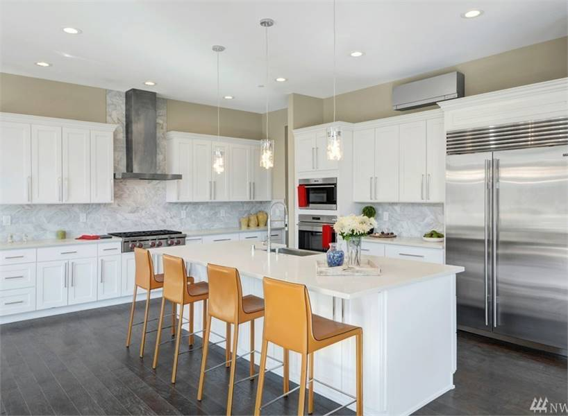 The kitchen is equipped with white cabinetry, marble backsplash, stainless steel appliances, and an immense breakfast island.